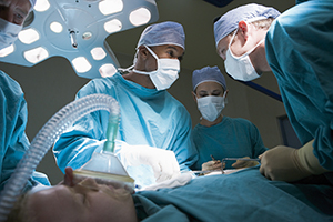 Three Surgeons Operating On A Patient